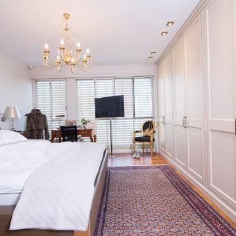 חדר הורים עם ארון לבן התופס קיר מלא ועל הפרקט שטיח בסגנון פרסי