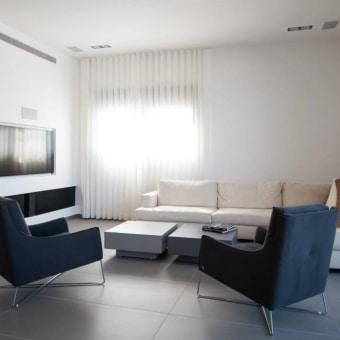 ספה לבנה לצד שתי כורסאות כחולות ואח מפנק מתחת לטלוויזיה