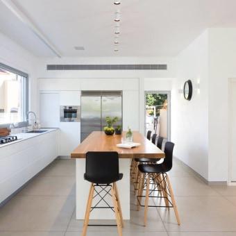אי לבן במטבח עם פלטת עץ וכיסאות שחורים