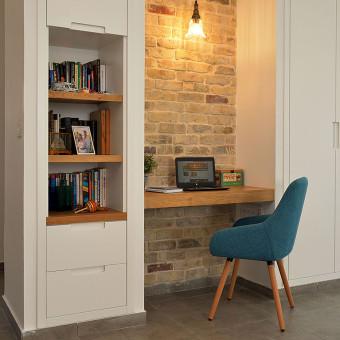 פינת העבודה ליד הסלון עם תאורה מלמעלה וארונית לספרים