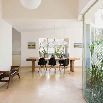 פינת אוכל מעץ מלא עם כיסאות שחורים. במבואת הכניסה, ספסל בעיצוב מצרי מודרני מעץ