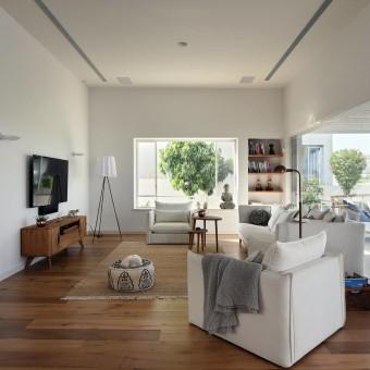 סלון לבן עם פרקט לצד פינת ישיבה לבנה במרפסת המופרדת בויטרינה