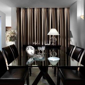 כיסאות שחורים ושולחן שחור עם פלטת זכוכית על רקע וילון בגווני חום שחור