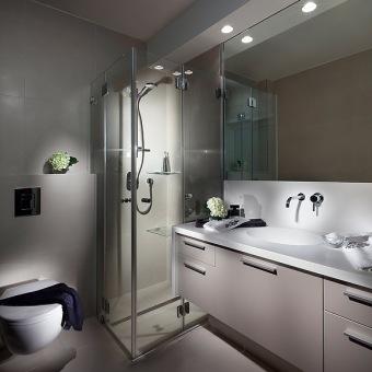 חדר רחצה יחסית קטן שמכיל הכל בגווני לבן ושמנת