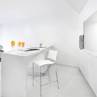 מטבח לבן עם קיר ארונות ואי במרכז המשמש גם כחוצץ לסלון