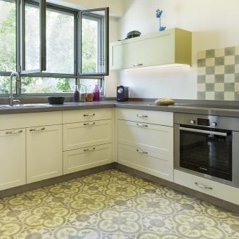 המטבח נפתח לגינה קדמית קטנה. הוא עוצב בגוונים של אפור וירוק, הקושרים אותו לגינה.