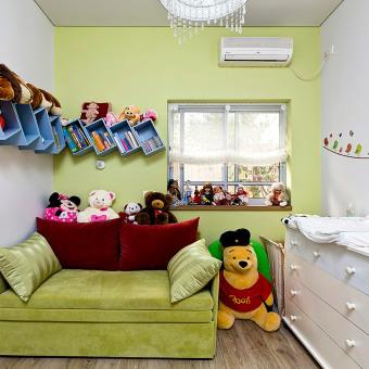 ספה ירוקה בחדר התינוקת לצד ארון החתלה לבן בעל מגירות רבות