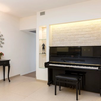 פינת פסנתר במרכז הבית עם מדפי גבס בקיר