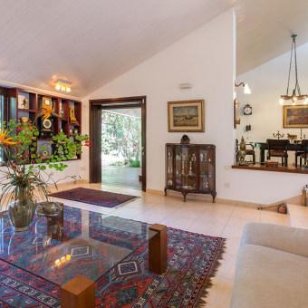 מבט אל הסלון ופינת האוכל. תקרת העץ, שהייתה חומה-כהה, נצבעה בצבע קרם בהיר.