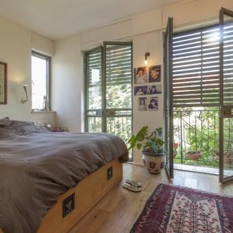 חדר השינה עם חלונות בלגים גדולים המכניסים תאורה טבעית