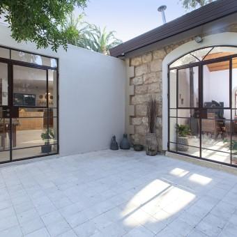 מבט לחיבור בין הבית הישן והחדש. החלונות עשויים מאותו חומר וצבועים בחום - אלא שבחלק הישן הם בעלי אופי נוסטלגי, ובחדש - בעלי קווים מודרניים יותר.