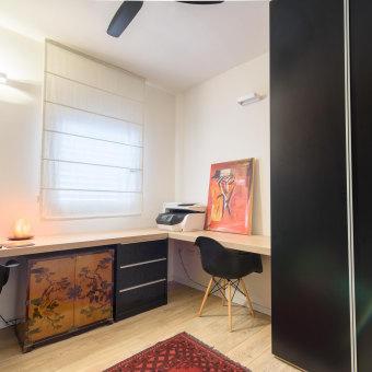חדר עבודה עם שולחן ריש אורך ושתי פינות ישיבה