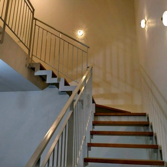 מדרגות ממדפי עץ ומעקה ברזל לבן