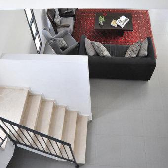 מדרגות בגוון שמנת לצד מעקה שחור