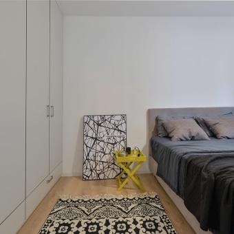 חדר השינה בסגנון סקנדינבי, השידה ליד המיטה הינה שולחן צהוב קטן עם רגלים באיקס