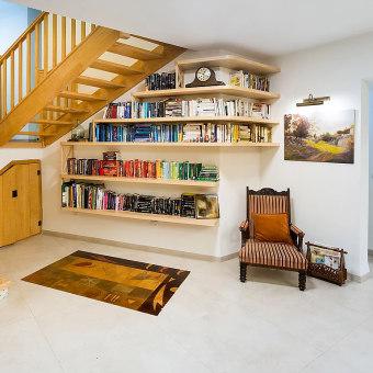 ספריה בצורת ריש לצד כורסא וינטג'ית מעץ כהה עם ריפוד בגוון אדום פסים