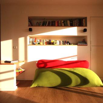 פינת משפחה עם שני מדפים מובנים בקיר לספרים ופוף ירוק מאורך