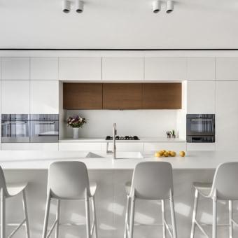 מטבח לבן ומודרני, פס עץ במרכזו לשבור את הצבע