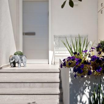 ספסל לבן ממתכת בכניסה לבית