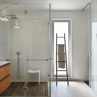 חדר הרחצה של ההורים עם ריצפת עץ במקלחת וקירות מרוצפים באבנים לבנות