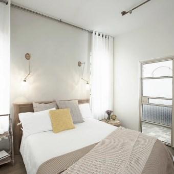 חדר השינה של ההורים בגווני חום בהיר ולבן, וילון לבן בשני צידיי המיטה