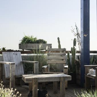 """למרפסת נוספה פרגולה שנצבעה בכחול, ריהוט החוץ הוכן ע""""י בעל הדירה -נגר במקצועו."""
