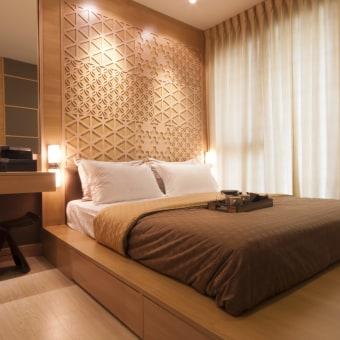 חדר הורים עם מיטה מוגבהת על במה וקיר דקורטיבי המוסיפים אווירה לתאורה המרגיעה