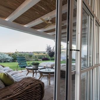 מבט מויטרינת הסלון אל המרפסת והשדות.