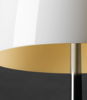 """A well-balanced and sophisticated presence, imposing yet not ostentatious, based on the contrast between the warmth of the glass diffuser – which is hand blown using a craft-based process – and the technology of the metal tripod. A further take on the concept of the classic bedside table, Lumiere XXS and XXL stands out for a clearer and more marked look compared to the """"historic"""" Lumiere."""