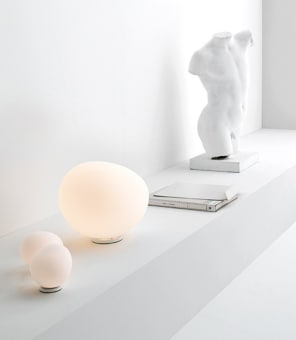 """Table or floor lamp with diffused light. White  satin finish hand-blown diffuser achieved  using glass blowing procedure without  turning the glass in the mould (referred to as  """"stationary""""), subject to immersion in acid.  The glass in the medium and large version is  incorporated with a matt transparent  injection moulded polycarbonate ring nut,  which is in white polycarbonate in the small  version. White epoxy powder coated metal  supporting base and matt injection moulded  transparent polycarbonate lamp holder  support. The dimmer for the gradual  brightness adjustment is fitted on the  transparent cable for large and black  medium version."""
