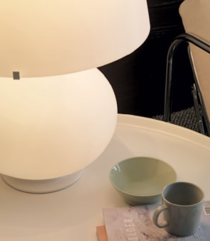 An exquisite object, almost entirely in white blown glass, composed of a round element that tapers slightly upward, surmounted by a truncated cone: the classic form of the abat-jour lamp that defined an era in lighting. The peculiarity of Fontana is its multiple light sources: both the base and the lampshade contain one or more. The larger version also allows indirect lighting, thanks to an additional source that projects a beam of indirect light upwards. The differentiated light sources make it possible to satisfy different lighting needs: from a soft, relaxing glow to a sharp beam for reading to suggestive ambient light. The soft and perfectly proportioned forms, the purity of the design and the milky opalescent finish combine to make it a timeless piece, perfect in every setting, whether turned on or off.