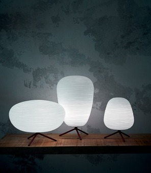 """Table lamp with diffused light. A collection of three diffuser shapes in hand-blown glass made using a glass-blowing procedure without turning the glass in the mould (referred to as """"stationary""""); the striped effect is achieved using a mould with negative decorations which are repeated across the surface of the glass, which is subsequently ground manually """"by belt"""" and which then undergoes immersion in acid in order to emphasise the plaster-like effect. The diffuser rests on a die cast zinc alloy tripod coated with epoxy powder paint with a rough finish on the metal surface. Available in two versions with G9 or E27 lampholder, the version with the G9 lampholder features a dimmer on the transparent cable for the gradual adjustment of brightness, while the version with the E27 lampholder is fitted with an on/off switch."""