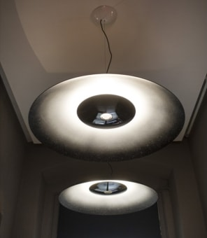 Suspension lamp with downward lighting.  The large diffuser is made from turned  aluminium with a black liquid coating. The  lamp's external coating has a special  textured effect, whereas the interior has a  matt finish. The reflective white colour on  the inside of the dome is created by hand in  three phases: the first gives a white shading  effect, the second goes over it again with  black in order to define the white area and  the final stage involves a coarse dripping  technique in white, increasing the casual  effect of the colour. This technique makes  every 'whitenoise' a unique piece that may  slightly differ from the next. The lower  diffuser, defining the beam of light, is made  from polished white ABS with an extremely  shiny, black liquid coating on the outside.  The inside of the diffuser is therefore  completely white in order to increase the  reflection of light, and glossy black on the  outside, creating a contrast with the matt  surface of the large dome. The diesel logo is  pad printed onto the outside of the diffuser.  The Citizen COB at the centre of the dome is  protected by a small diffuser made from  satin-finish polycarbonate. The suspension  cable is made from stainless steel and the  electrical cable is covered with a black  material casing. The ceiling rose has a  galvanised metal bracket which houses the  transformer and a glossy white cover made  from batch-dyed ABS.