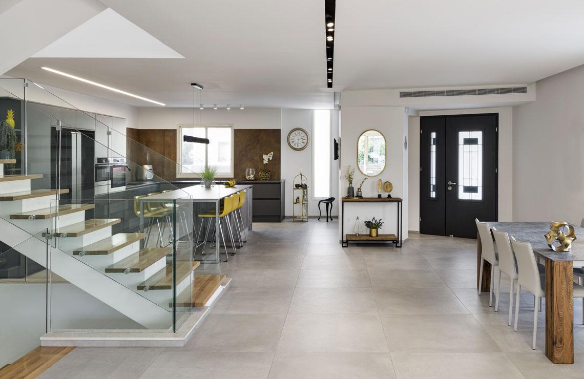 מבט מהסלון לכניסת הבית הצמודה למטבח מודרני