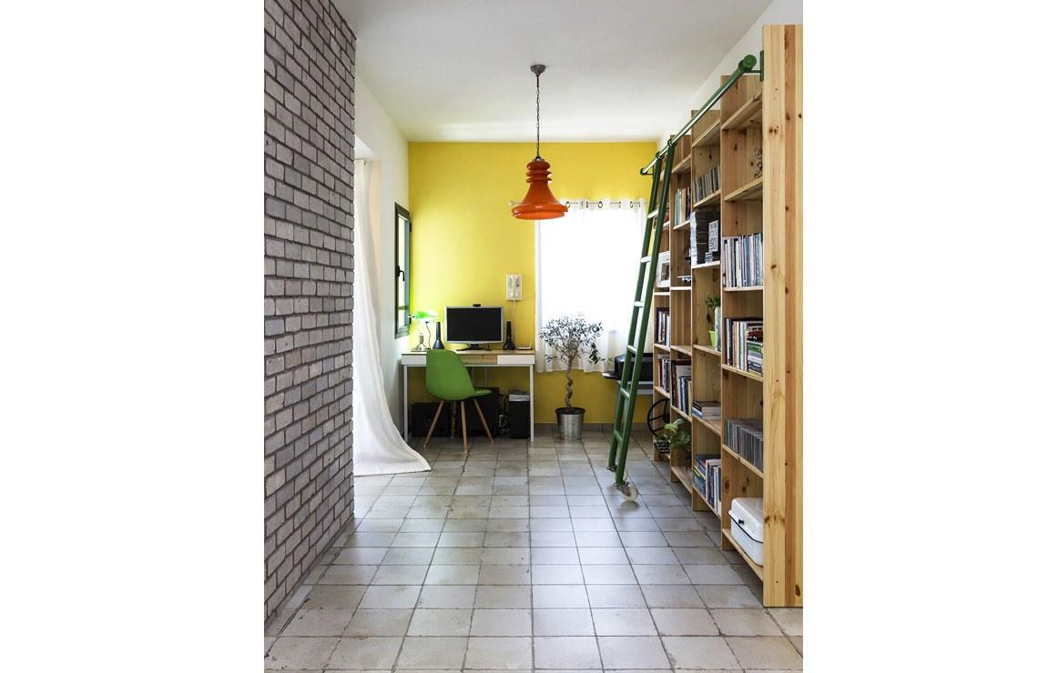 חדר עבודה מואר באור טבעי, יחד עם שילוב ספריה דקורטיבית