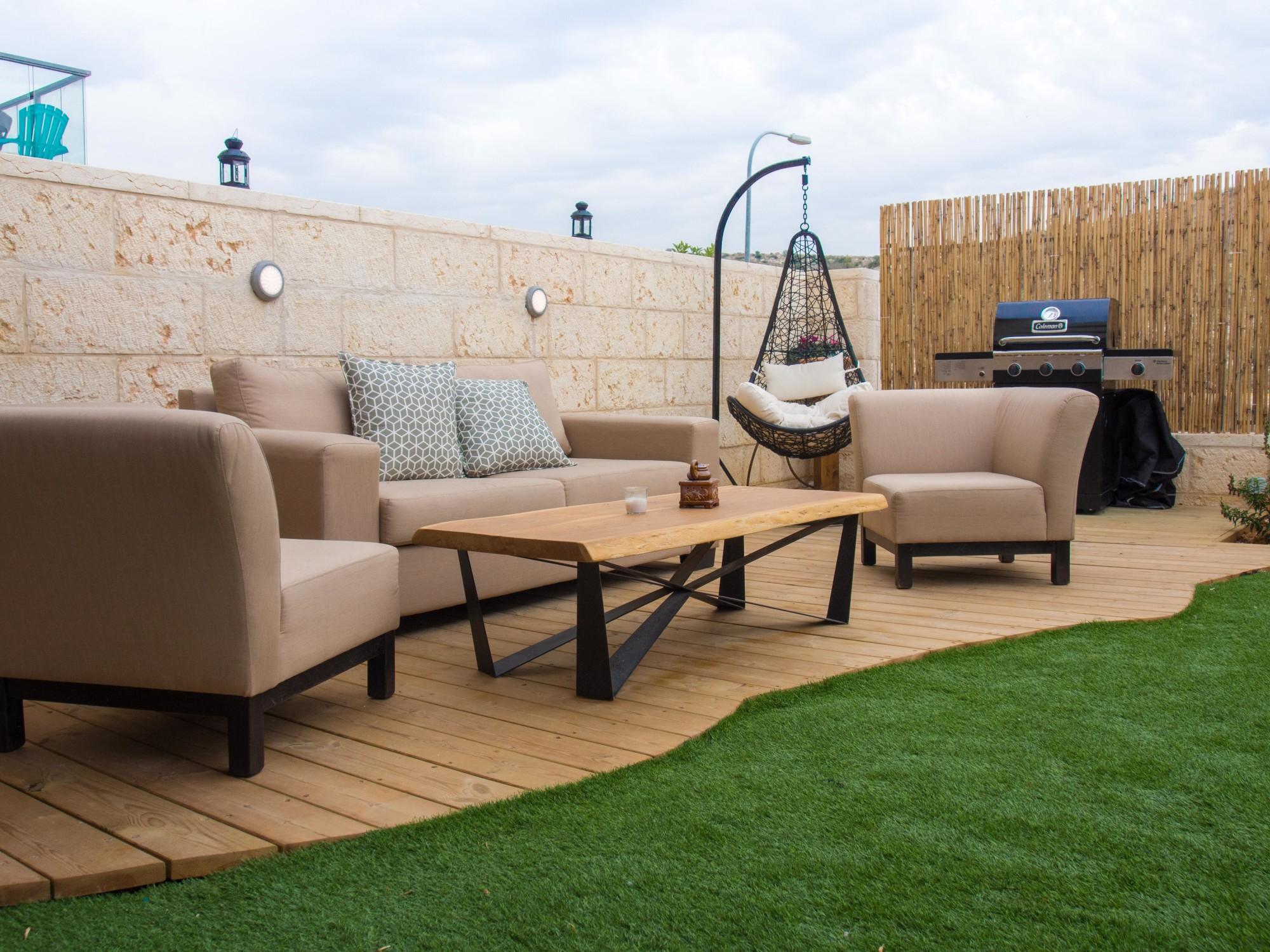 פינת ישיבה בגינה המונחת על דק עץ בהיר כהמשך לצבעוניות הבית