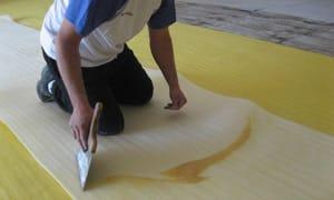 A continuación se esparce el adhesivo sobre el piso, en la superficie a ocupar, por el Base para Alfombras y sobre la cara inferior del Base para Alfombras ISOLANT (color blanco).