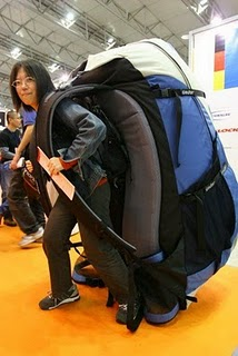 Foto divertida de una chica con una mochila enorme