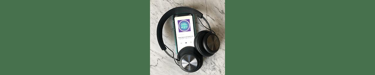 Phone displaying Del Reydio podcast with headphones