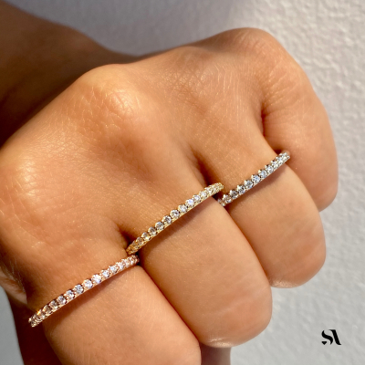 women fist displaying 14k round diamond dainty band in three gold tones