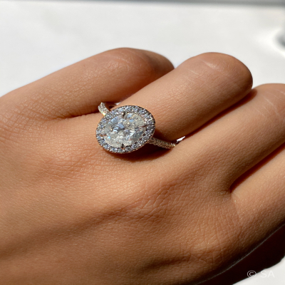 oval diamond halo engagement ring on finger
