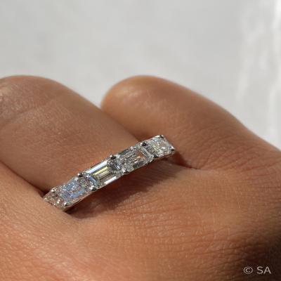 east west emerald cut eternity band on finger