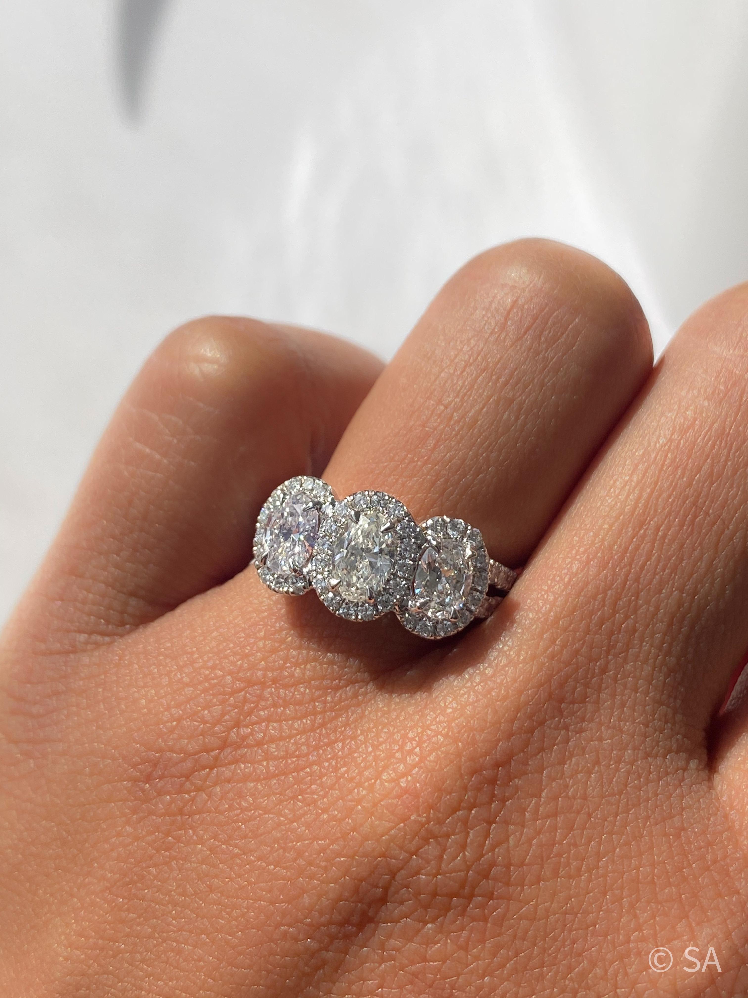 3 stone halo engagement ring on finger