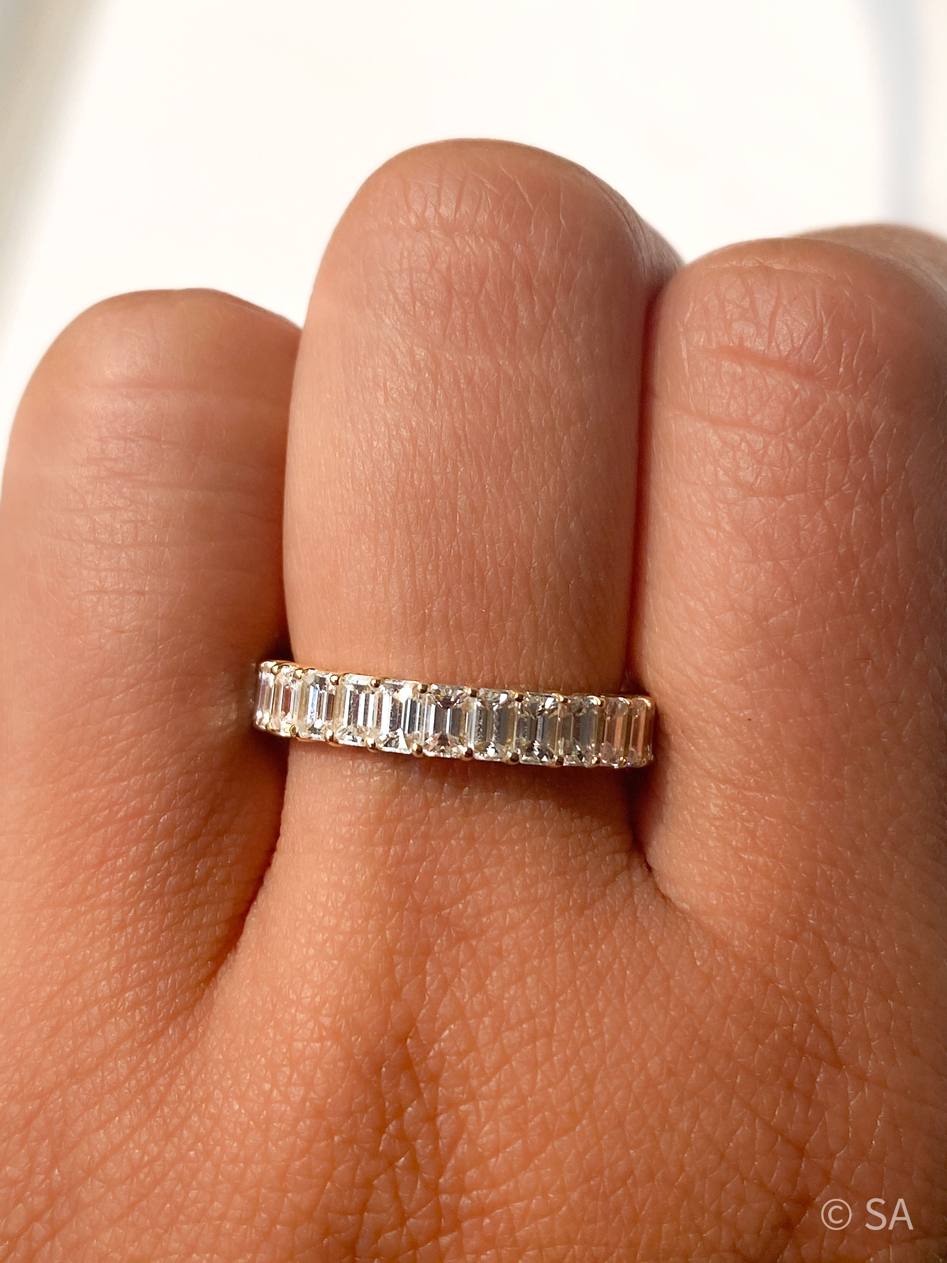 petite diamond band on finger