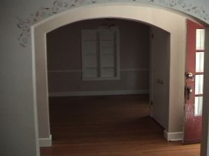 Vidw of dining room with wood floors, arched entryway