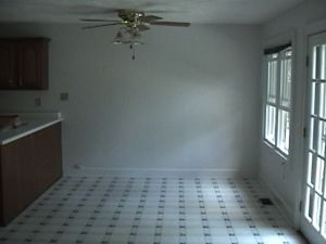 View of breakfast nook with black and white tile floor and door and window on right. There's a ceiling fan.