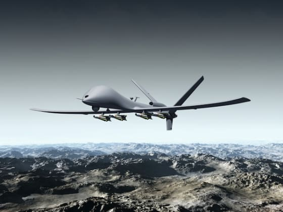 Illustration of a combat drone flying over barren mountains  by Paul Fleet via Shutterstock.com