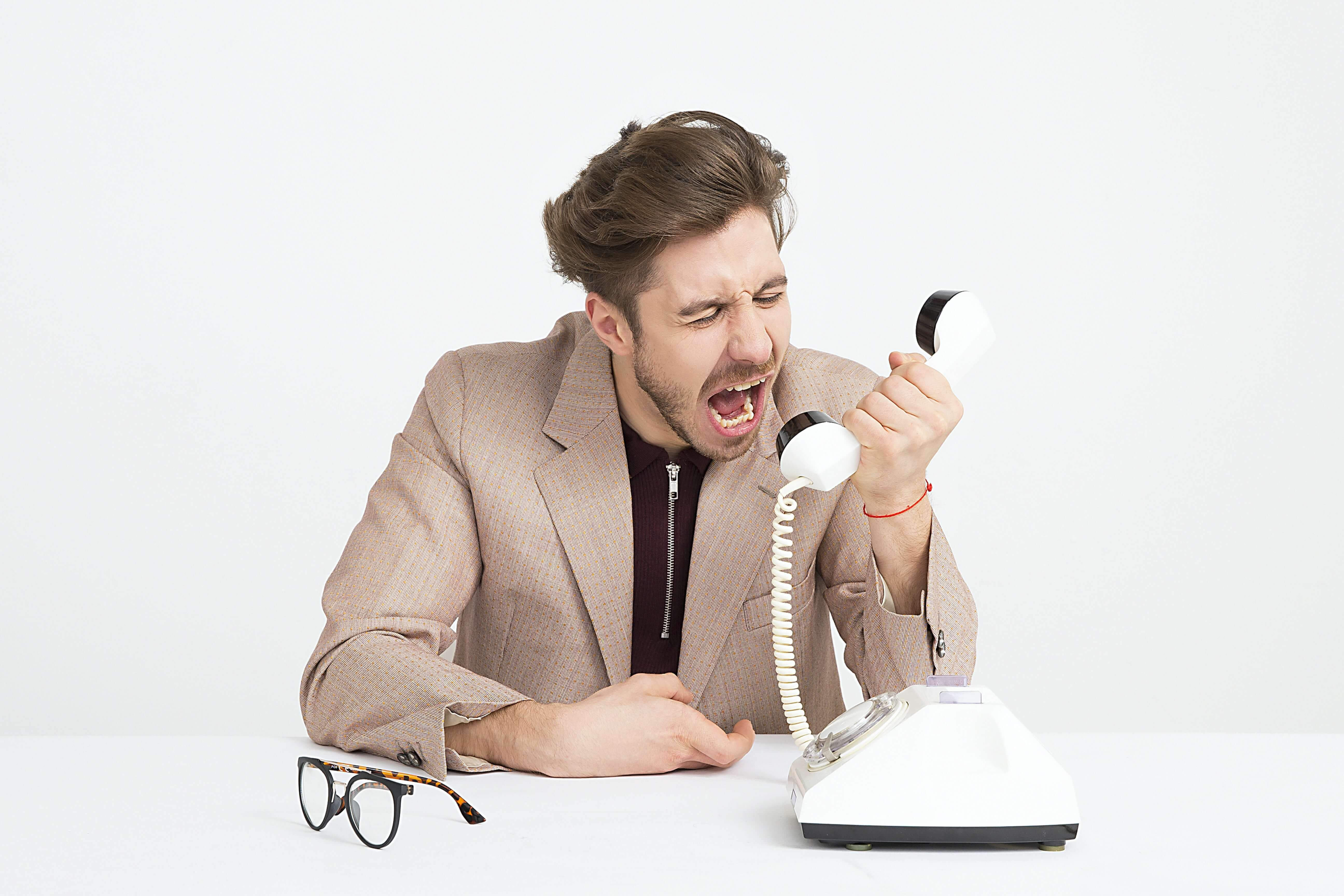 Image of a frustrated man on the phone.
