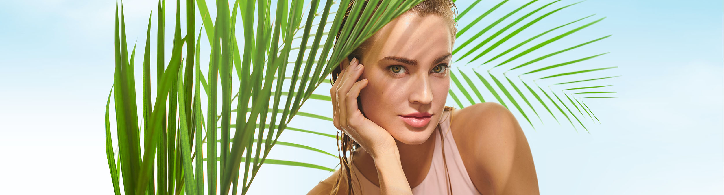 A sun-kissed woman looks through some palm tree leaves