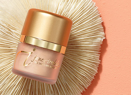 Powder-Me SPF product bottle on a peach background